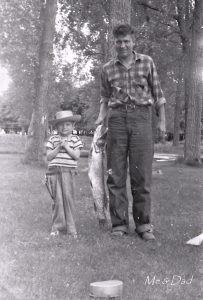young child in cowboy hat, holster and cap gun, father holding a large fish
