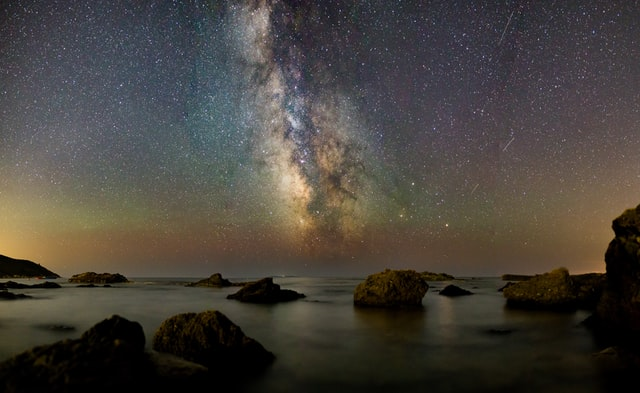 bay. stars, water, glowing clouds on horizons